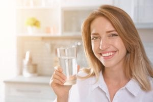Young Woman With Glass Of Clear Water In Kitchen. Refreshing Dri